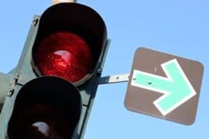 Das Verkehrsschild: Ein grüner Pfeil auf schwarzem Grund.
